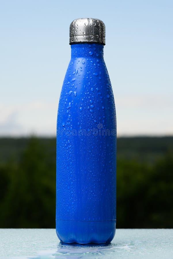 Bouteille inoxydable thermo, pulvérisée avec de l'eau Ciel et forêt sur le fond Sur le bureau en verre Thermos de couleur bleue m images stock