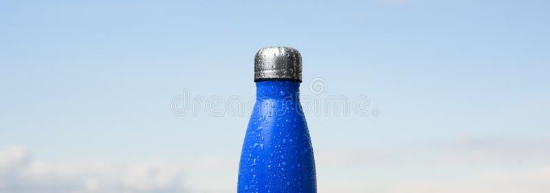 Bouteille inoxydable thermo, pulvérisée avec de l'eau Ciel et forêt sur le fond Thermos de couleur bleue mate images libres de droits