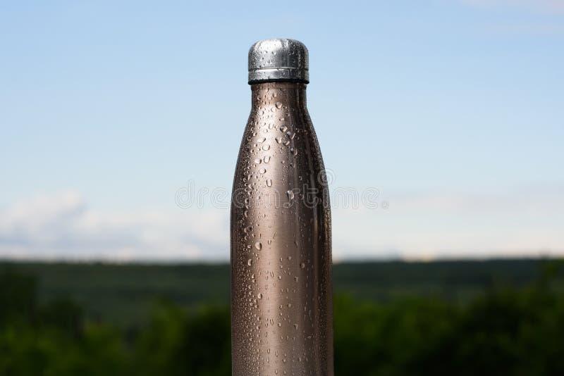 Bouteille inoxydable thermo, pulvérisée avec de l'eau Ciel et forêt sur le fond Thermos de couleur de maro photographie stock libre de droits