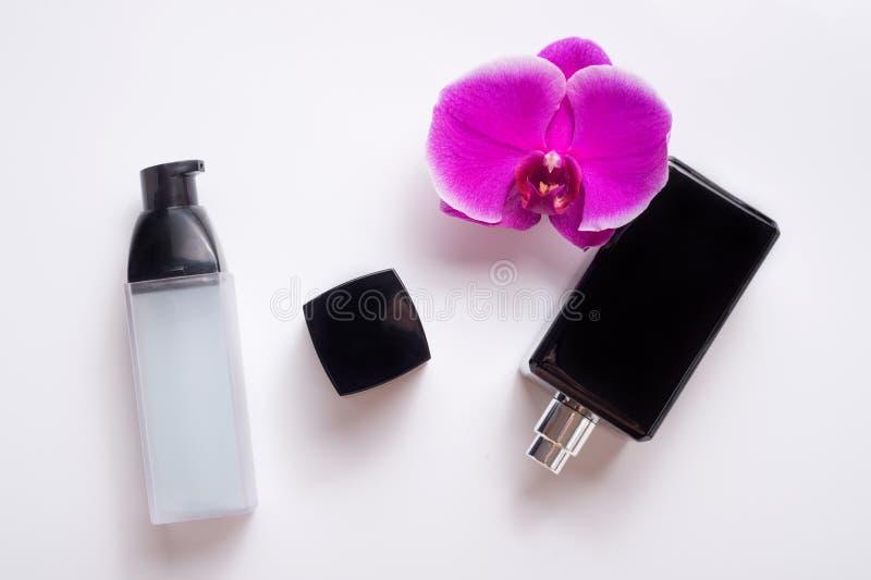 Bouteille noire de parfum avec l'orchidée pourpre et essence précieuse pour la jeunesse autour du blanc Configuration plate image stock