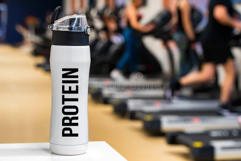 Bouteille ou tasse en plastique avec la boisson de protéine dans la fin de gymnase  image libre de droits