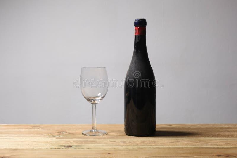 Bouteille poussiéreuse de vin chevronné rouge et un repos en verre vide sur une table en bois avec l'espace de copie pour votre image stock