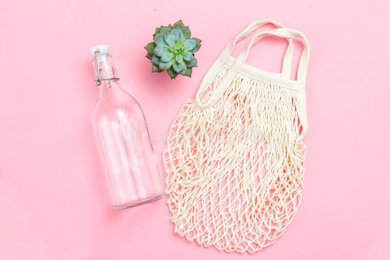 Bouteille réutilisable et sac à filet réutilisable sur fond rose Vie durable Plantes succulentes image stock