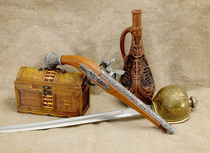 Bouteille, rapière, épée, pistolet et coffre image libre de droits