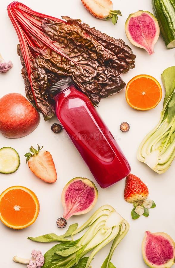 Bouteille rouge de smoothie avec les ingrédients sains de fruits et légumes sur le fond blanc de bureau, vue supérieure, configur image libre de droits