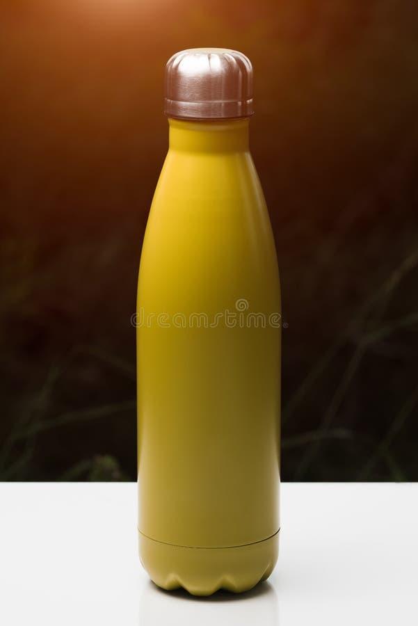 Bouteille thermo inoxydable pour l'eau, le thé et le coffe, sur la table blanche Fond foncé d'herbe avec l'effet de lumière du so photo stock
