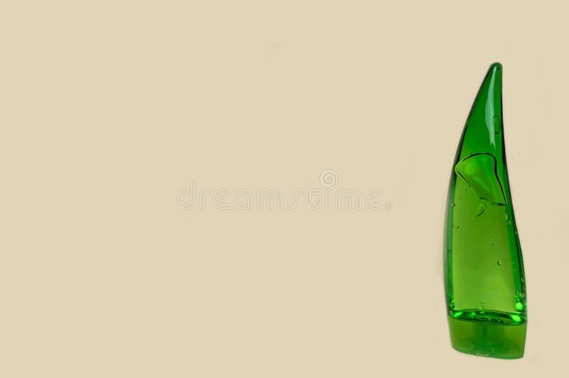 Bouteille verte avec le gel cosmétique d'aloès sur un fond jaune photos libres de droits