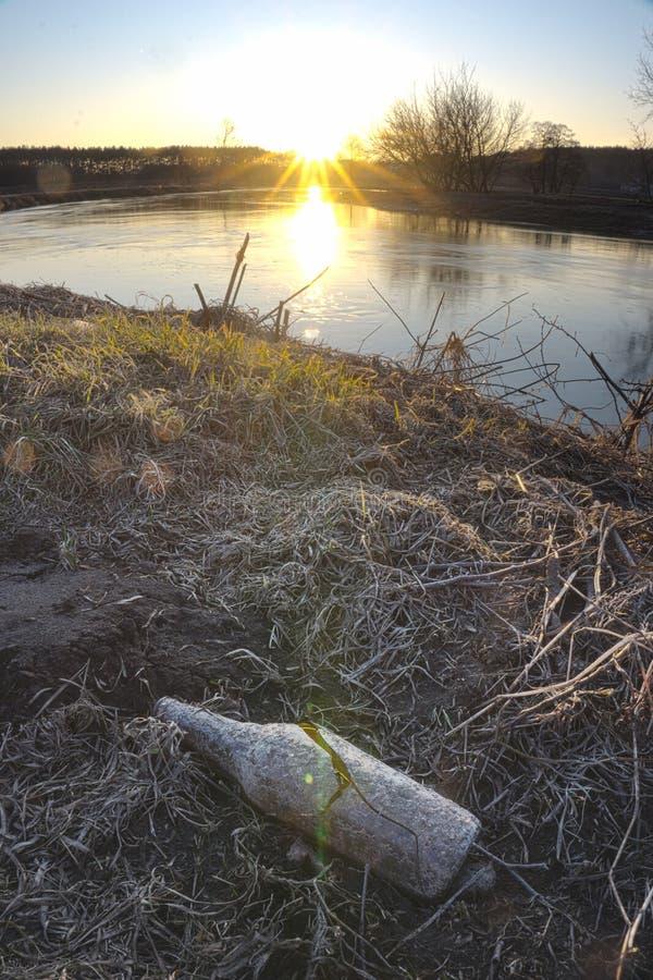 Bouteille vide en verre cassée dans le domaine par la lumière du coucher de soleil photos libres de droits