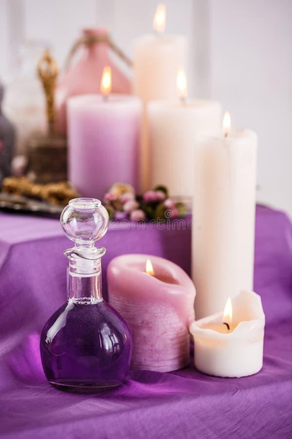 Bouteilles avec de l'huile d'arome et les bougies essentielles d'arome Configuration de station thermale photo stock