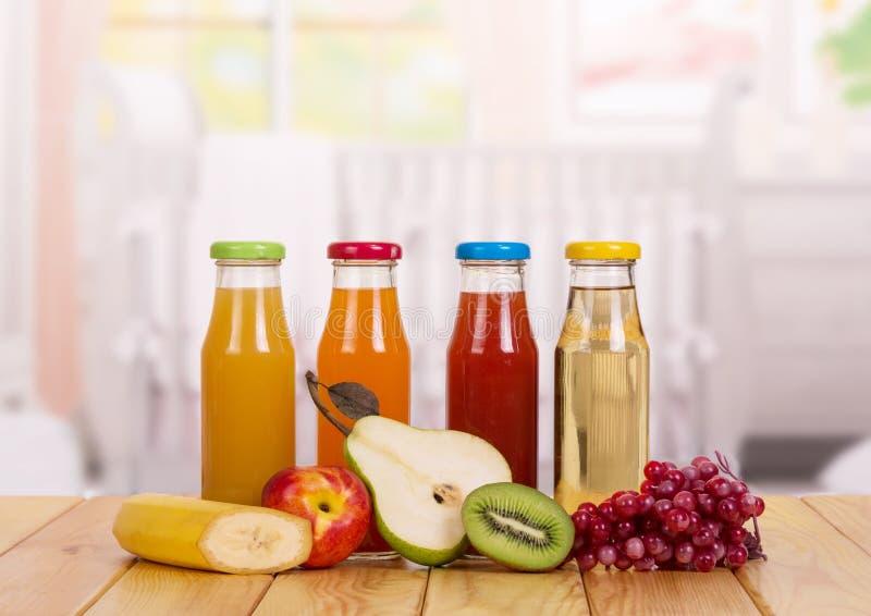 Bouteilles avec des fruits frais de jus sur la cuisine de fond blanc cru de macaronis de nourriture de fond de chéri photo libre de droits