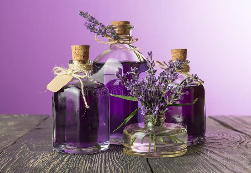 Bouteilles avec la teinture de décoction et de lavande avec des bouchons et le label, fleurs dans le vase, sur la table photographie stock