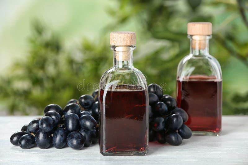 Bouteilles avec le vinaigre de vin et les raisins frais sur la table en bois images stock