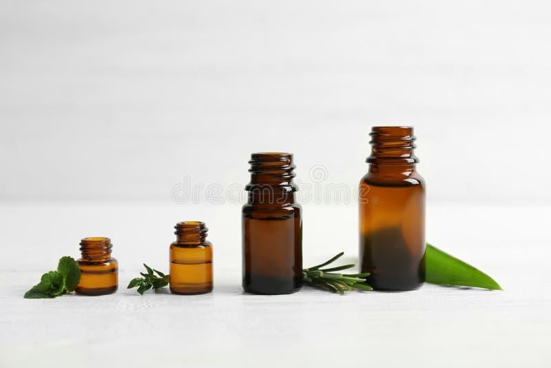 Bouteilles avec les huiles essentielles et les herbes fraîches photographie stock