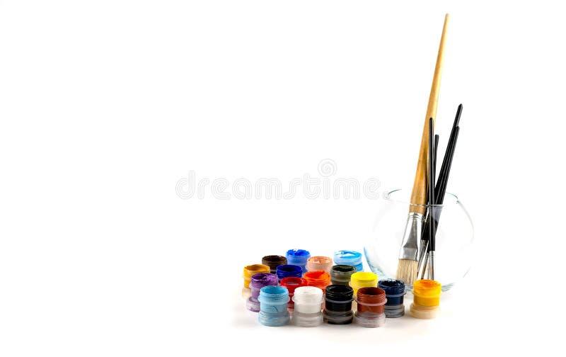 Bouteilles avec les peintures acryliques de diverses couleurs et des brosses dans un vase en verre photo stock