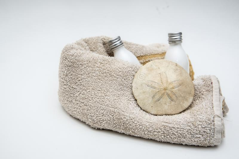 Bouteilles blanches serviette de lotion et dollar de sable images stock