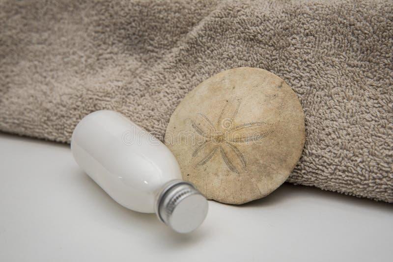 Bouteilles blanches serviette de lotion et dollar de sable image stock