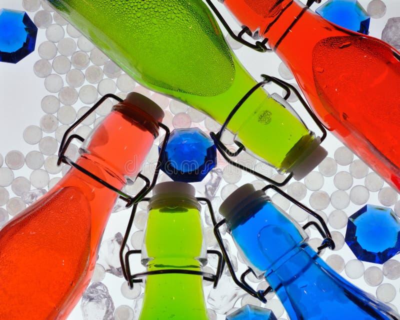 Bouteilles colorées éclairées à contre-jour photographie stock libre de droits