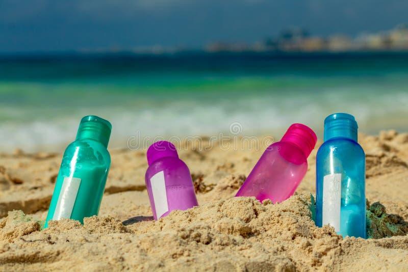 Bouteilles colorées dans le sable image libre de droits