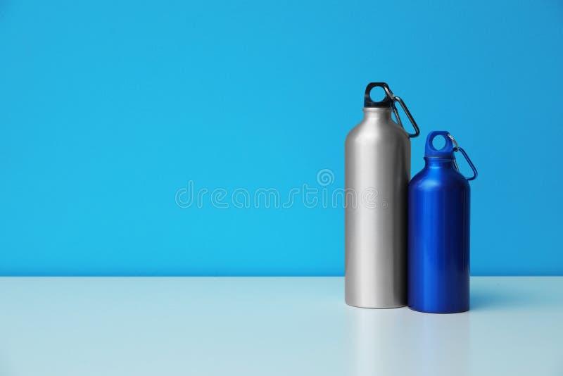 Bouteilles d'eau en aluminium pour des sports sur le fond de couleur image libre de droits