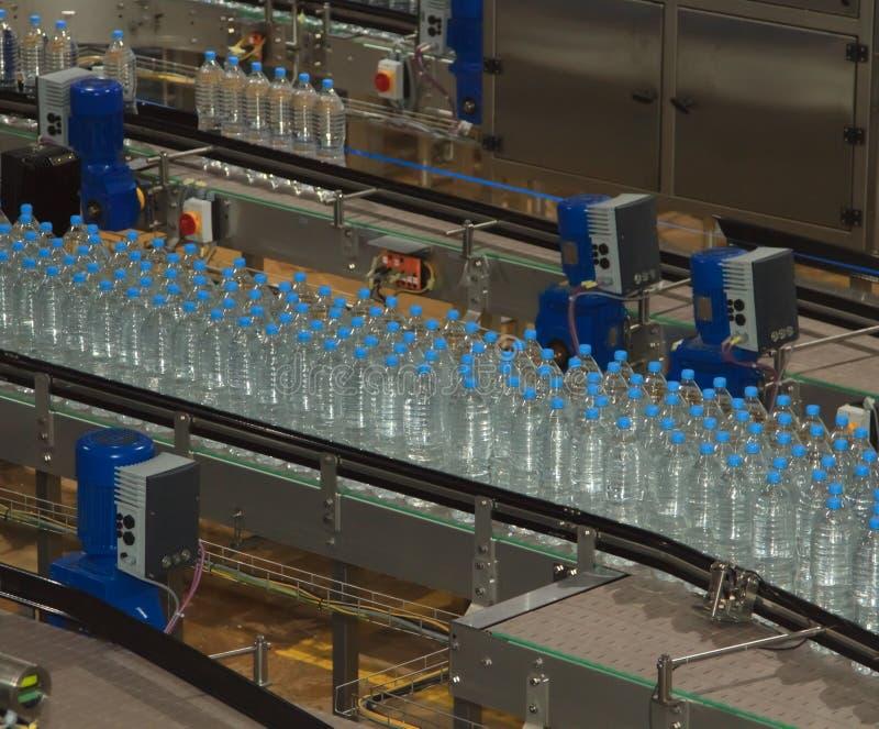 Bouteilles d'eau en plastique sur la machine d'embouteillage de convoyeur et d'eau images libres de droits