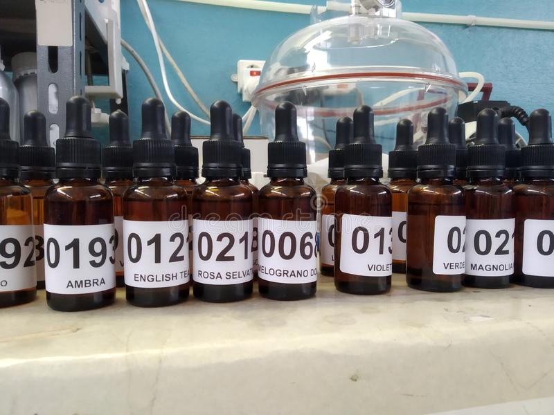 Bouteilles d'essence de parfum petites et cloche brunes de vide photo stock