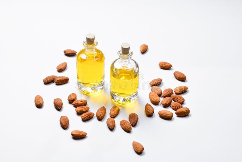 Bouteilles d'huile d'amandes et d'amandes sur le fond blanc, copyspace images stock