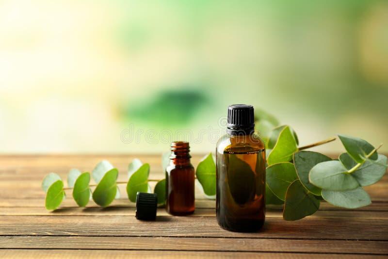 Bouteilles d'huile essentielle d'eucalyptus sur la table en bois photographie stock libre de droits
