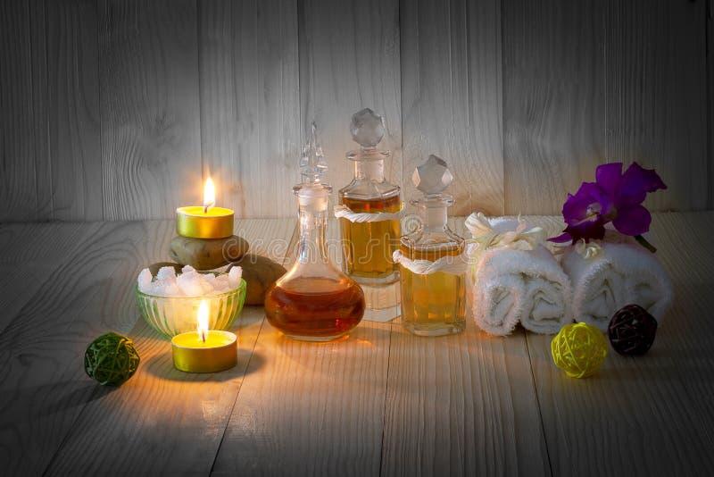 Bouteilles d'huiles aromatiques avec les bougies, l'orchidée rose, les pierres et la serviette blanche sur le fond en bois de vin images libres de droits