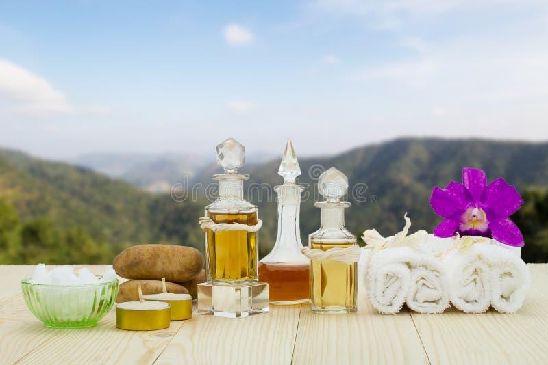 Bouteilles d'huiles aromatiques avec les bougies, l'orchidée rose, les pierres et la serviette blanche sur le plancher en bois de image libre de droits
