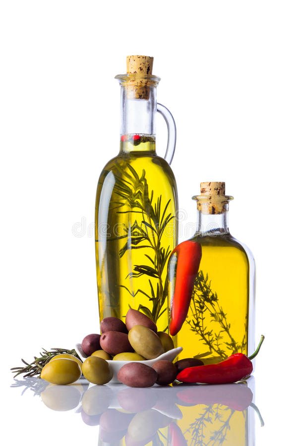 Bouteilles d'Olive Oil avec le poivre et les herbes sur le blanc image stock