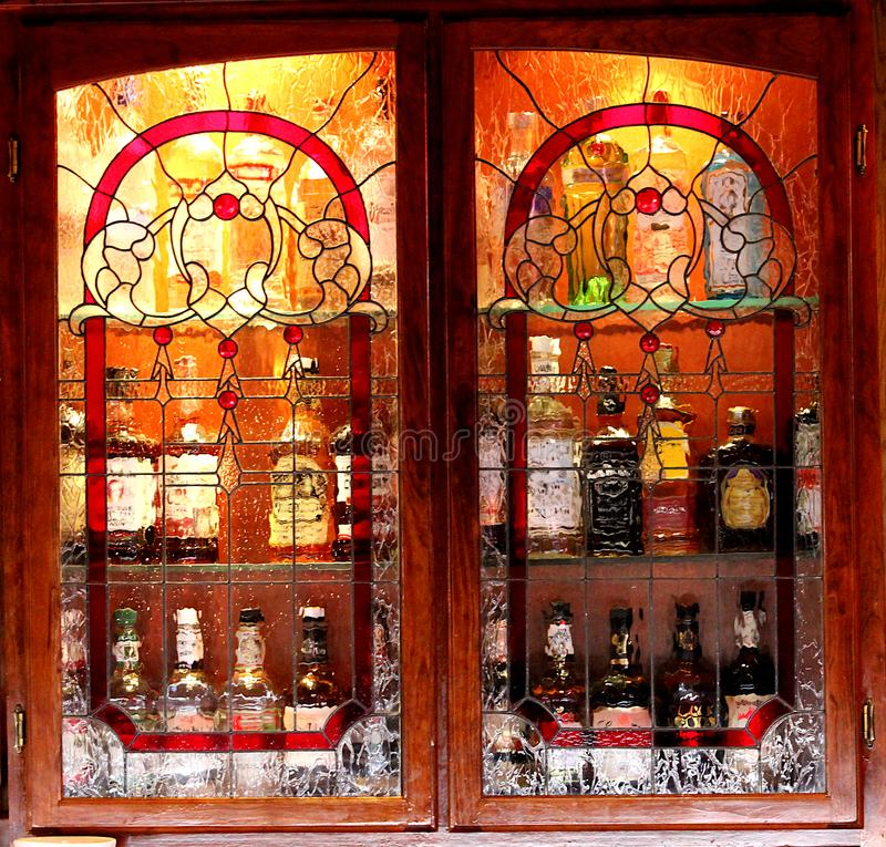 Bouteilles de boisson alcoolisée brouillées derrière l'armoire en verre souillée images stock