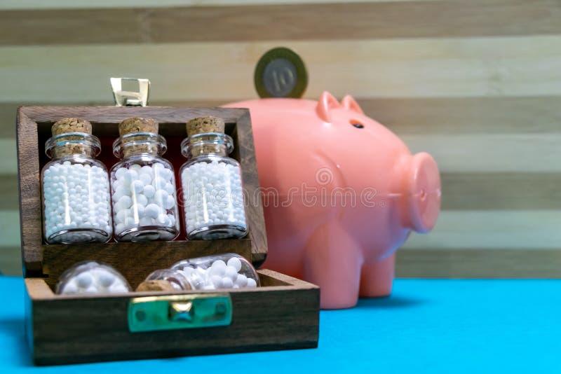 Bouteilles de médecine homéopathique dans la vieille boîte en bois et d'une pièce de monnaie sur la tirelire rose avec la surface photo stock