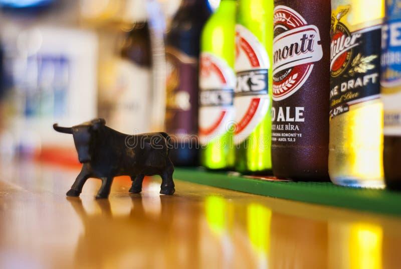 Bouteilles de miniature et à bière de Taureau sur un compteur de barre photos stock