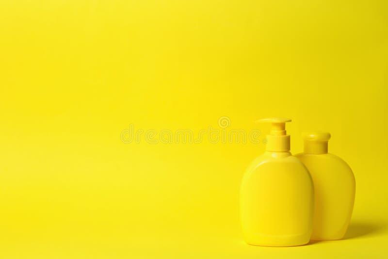 Bouteilles de shampooing sur le fond jaune Produits cosm?tiques naturels image libre de droits
