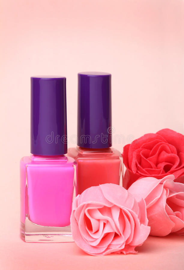 Bouteilles de vernis à ongles et fleurs roses image stock