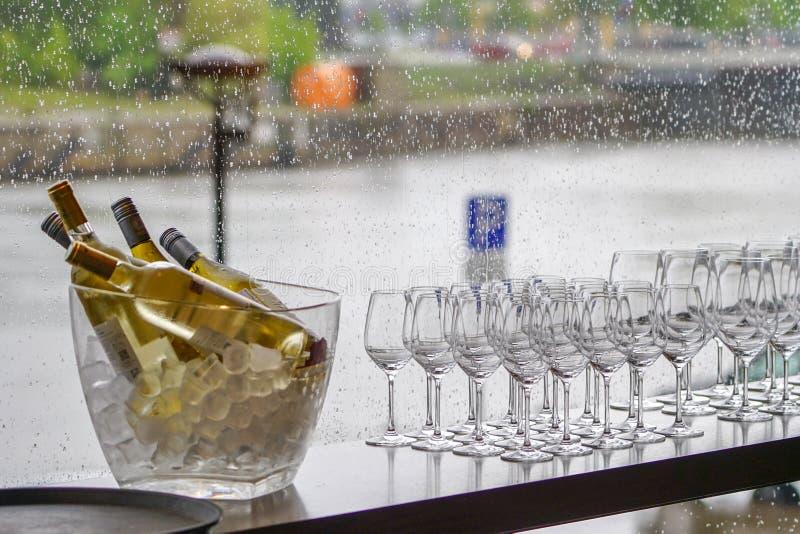 Bouteilles de vin dans la cuvette avec des glaçons, beaucoup de verres sur un fond pluvieux de fenêtre image libre de droits