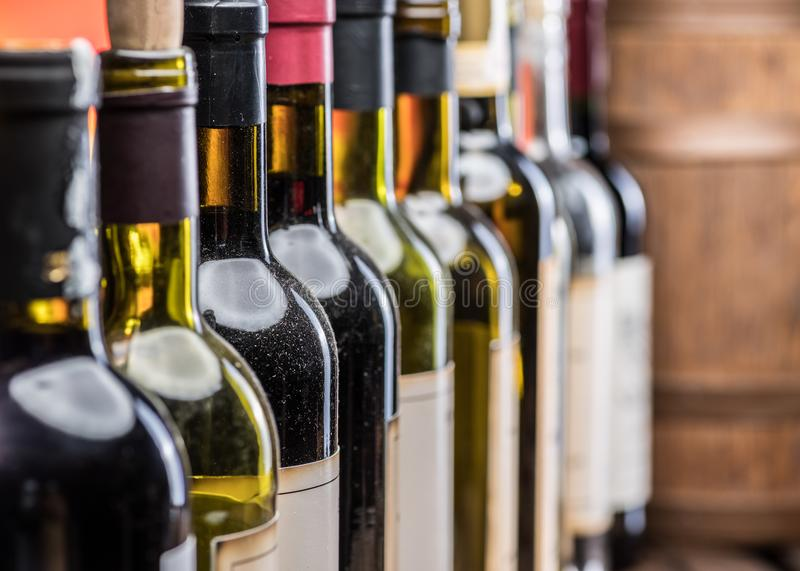 Bouteilles de vin dans la rangée et le barillet de vin de chêne photo stock