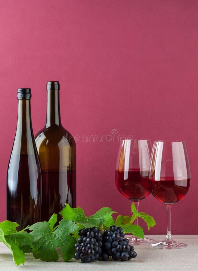Bouteilles de vin et glassess avec des raisins photographie stock