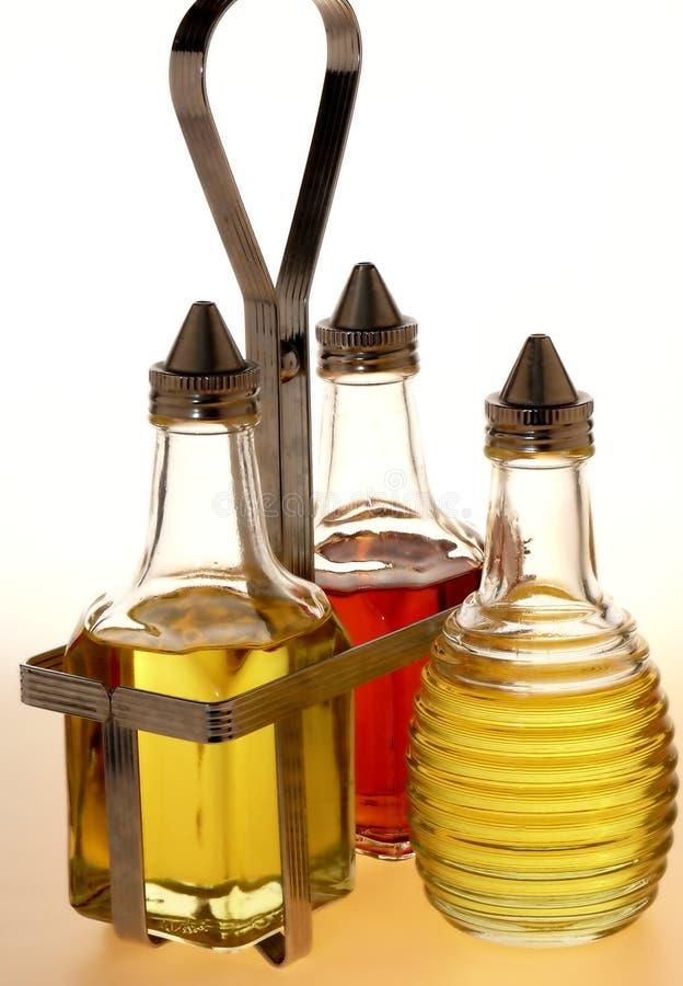 Bouteilles de vinaigrette et armoire en métal photographie stock libre de droits
