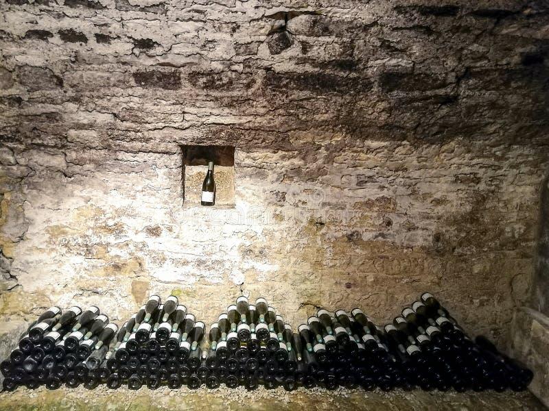 Bouteilles empilées dans une cave française image stock