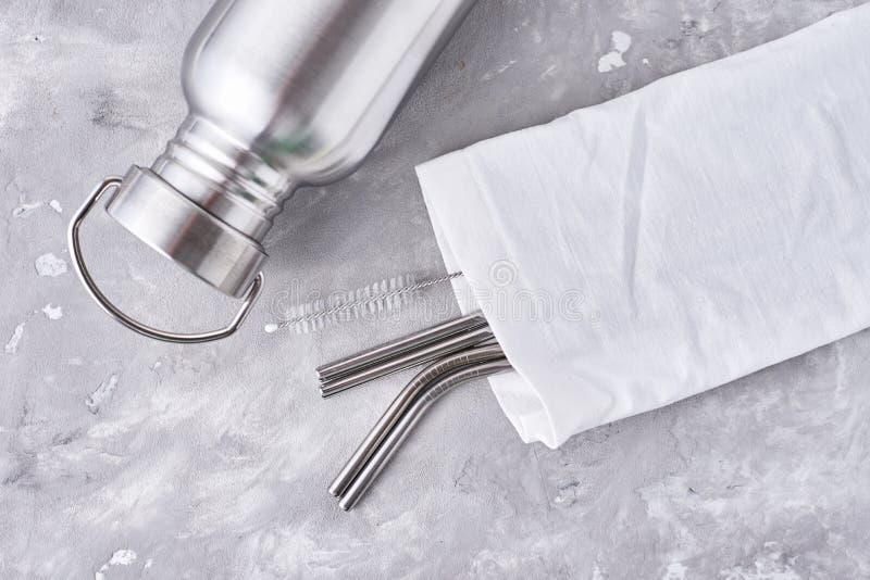 Bouteilles en aluminium et tubes en métal dans un sac en coton sur fond gris Objets écologiques réutilisables Concept écologique  photos libres de droits
