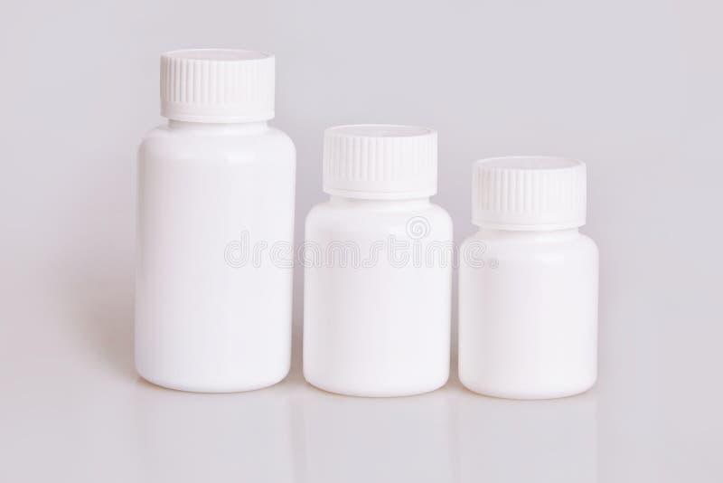 Bouteilles en plastique médicales de blanc blanc de différentes tailles sur un fond blanc images stock