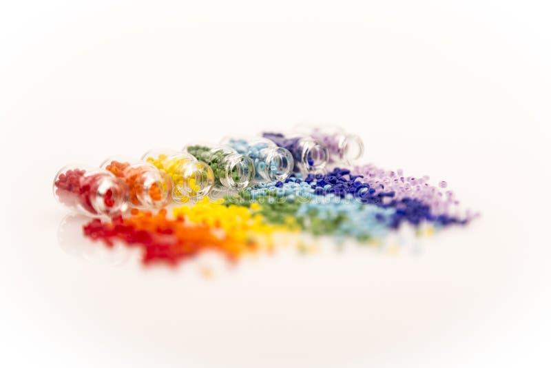Bouteilles en verre minuscules avec un arc-en-ciel des perles photos stock