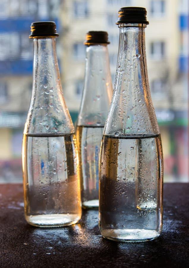 Bouteilles en verre remplies avec de l'eau demi dans la lampe au néon sur le fond de la vue à partir de la fenêtre Foyer s?lectif image libre de droits