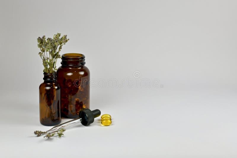 Bouteilles m?dicales en verre fonc?es, thym sec, capsules d'huile et une chapeau-pipette photographie stock libre de droits