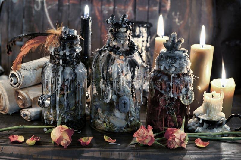 Bouteilles magiques avec les bougies, les rouleaux et les fleurs brûlants sur la table de sorcière photo stock