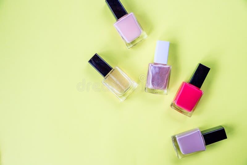 Bouteilles multicolores avec le vernis à ongles présenté sur un fond jaune Bouteille de vernis ? ongles Salon de beaut? trendy photos stock