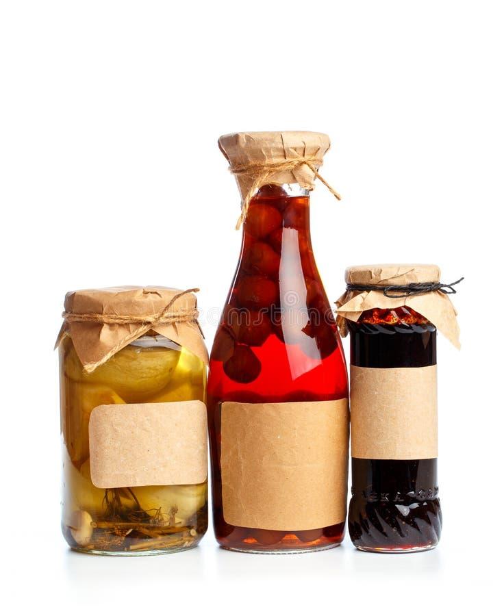 Bouteilles réglées en verre d'og avec la nourriture conservée sur le fond blanc images stock