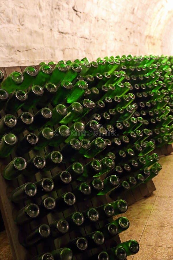 Bouteilles vertes dans la cave photographie stock libre de droits