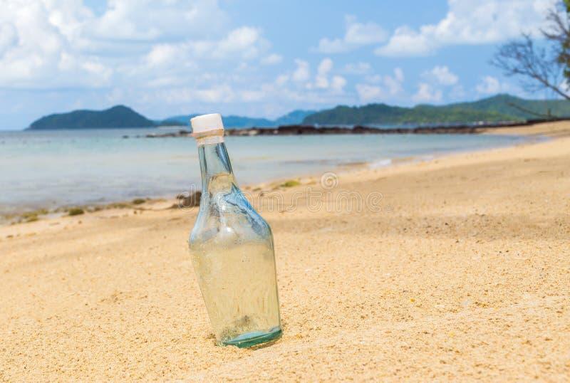 Bouteilles vides sur la plage de sable images libres de droits